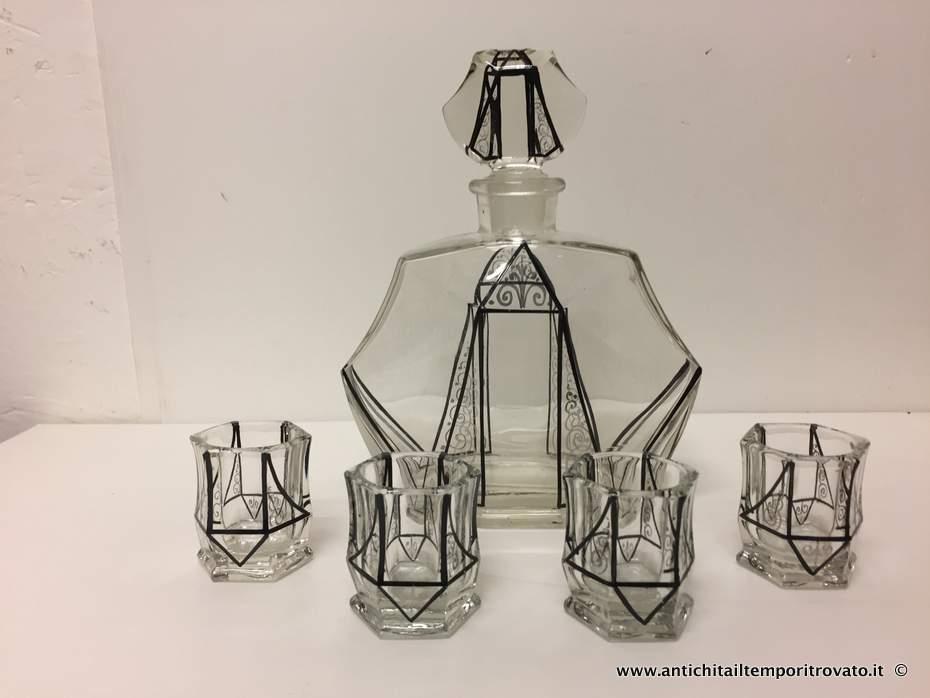 Oggettistica d`epoca → Vetri e cristalli → Bottiglia deco  Antica ed elegante bottiglia da rosolio dèco di forma geometrica (17x8; h.21) con 4 piccoli bicchieri esagonali (Ø5; h.5,5) decorata in nero e argento. Ottimo lo stato di…  ... continua ...