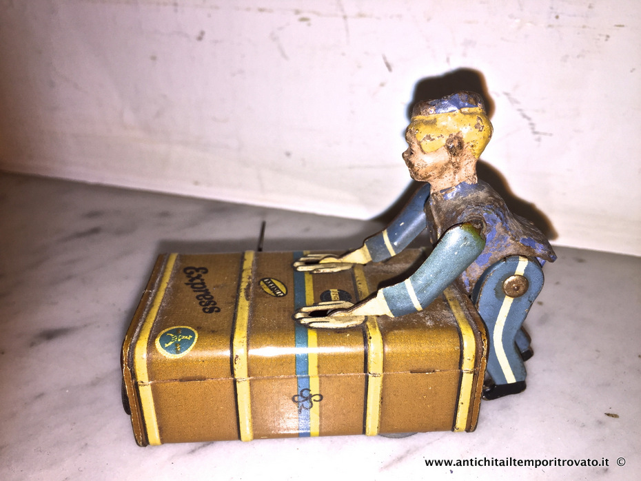 Giocattoli antichi → Giocattoli in latta → Antico giocattolo: ragazzo con valigia  Infaticabile Bell Boy Toy, giocattolo a carica manuale realizzato nel 1930 in Germania occidentale dalla ditta Gescha, produttrice di giocattoli, fondata a Norimberga nel 1923. Il giocattolo è…  ... continua ...